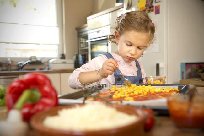 Girl in kitchen preparing pizza — Stock Photo