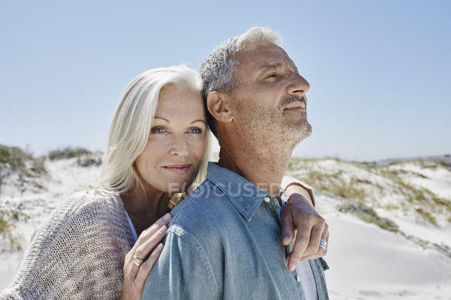 Pareja madura abrazándose en la playa - foto de stock