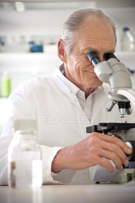 Professor in laboratory examining samples under microscope — Stock Photo