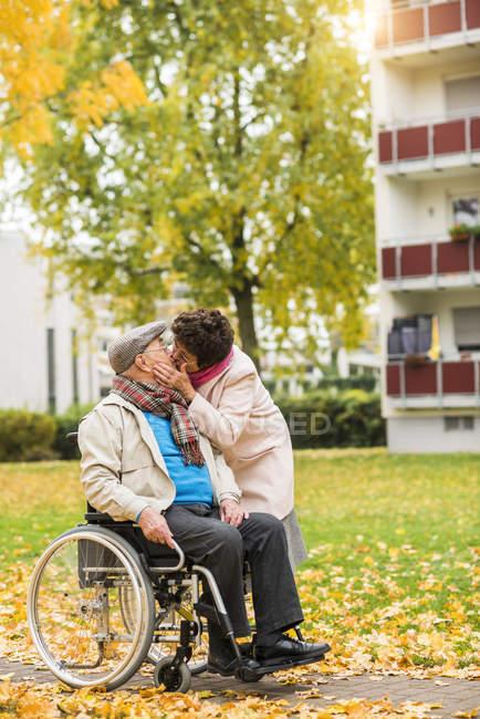 Femme âgée embrasser mari en fauteuil roulant — Photo de stock