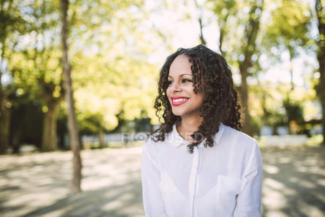 Femme avec des annelets marchant dans le parc — Photo de stock