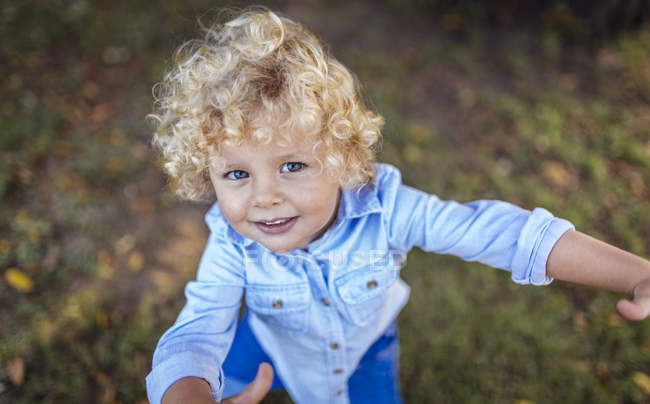 Portrait of smiling blond little boy looking up to camera — Stock Photo