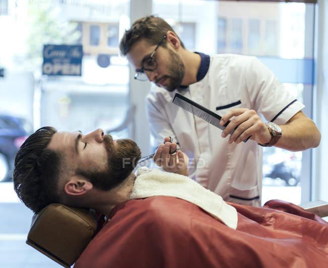 Barber cutting beard of a customer in barbershop — Stock Photo