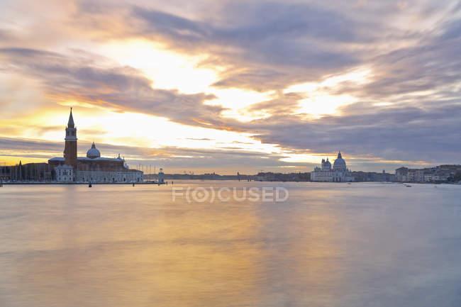 Italia, Venecia, Vista de la isla San Giorgio Maggiore y la Basílica de Santa Maria della Salute en la luz del atardecer - foto de stock