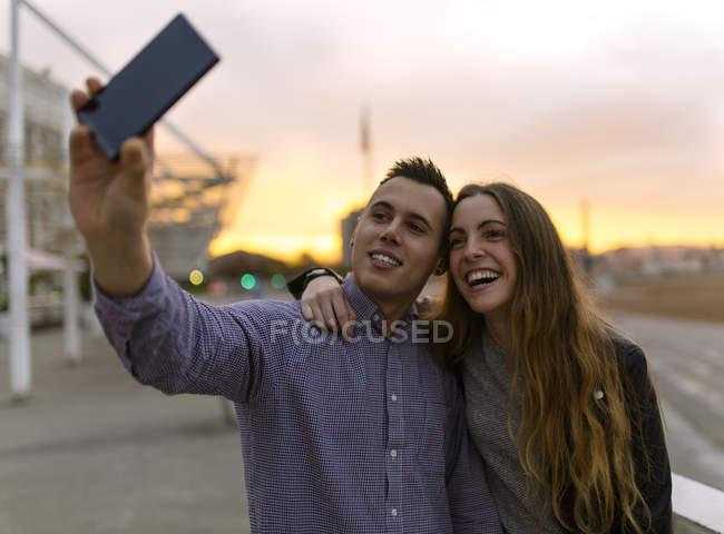 Junges Paar unter einem Selfie mit Smartphone in der Abenddämmerung — Stockfoto