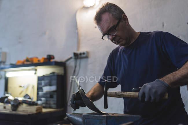 Schmiede hämmert Metall in Werkstatt — Stockfoto