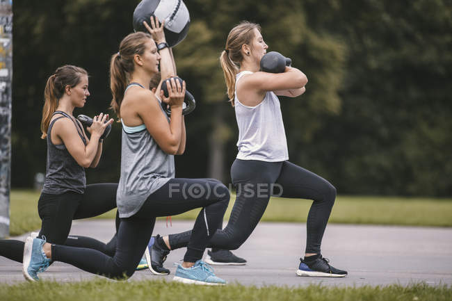 Four women having outdoor boot camp workout with kettlebells and ball — Stock Photo