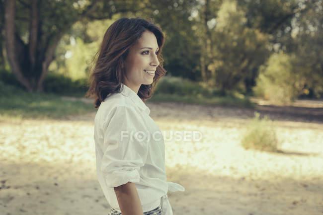 Retrato de mujer sonriente mirando a la distancia - foto de stock