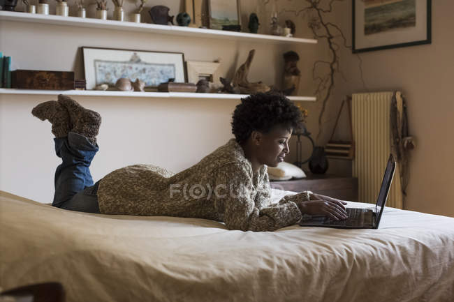 Young woman lying on bed using laptop — Stock Photo