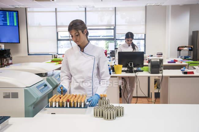 Technicien de laboratoire au laboratoire d'analyse prenant des éprouvettes d'un conteneur de centrifugeuse — Photo de stock