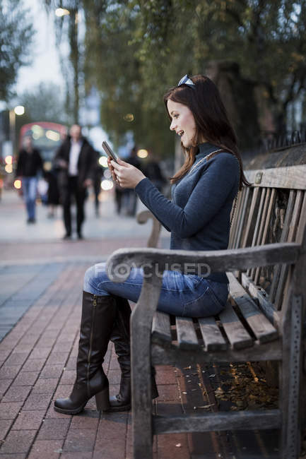 Happy woman looking at smartphone on a bench — Stock Photo