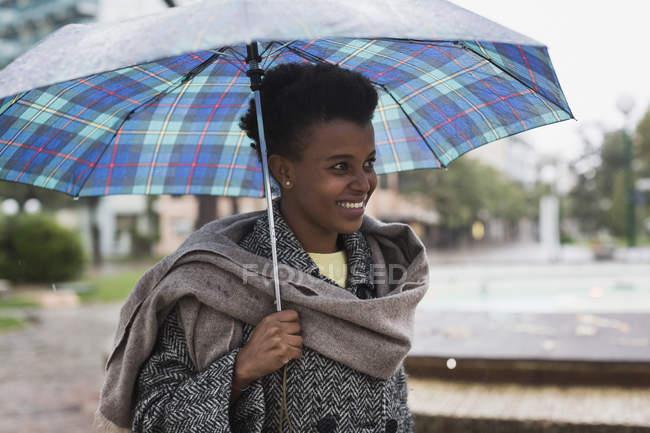 Femme souriante avec parapluie un jour de pluie — Photo de stock