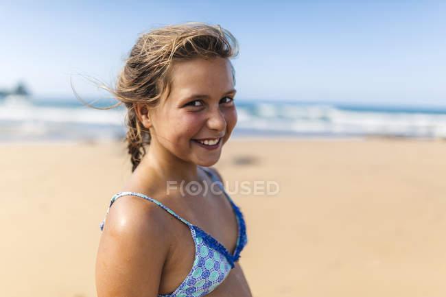 Portrait of smiling girl wearing bikini top on the beach — Stock Photo