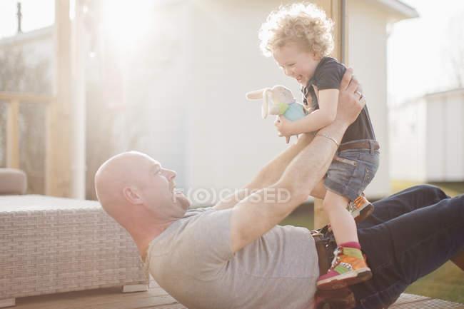 Père jouant avec la petite fille sur la terrasse — Photo de stock