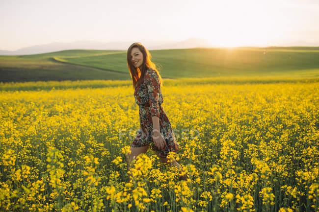 Jovem sorridente caminhando em um campo de estupro ao pôr do sol — Fotografia de Stock
