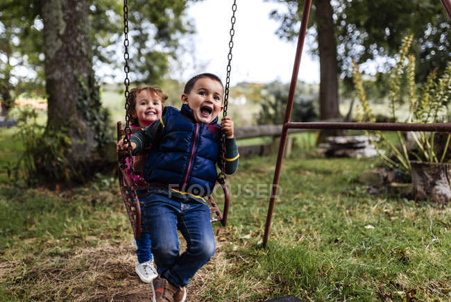 Toddler children playing with swing in garden — Stock Photo