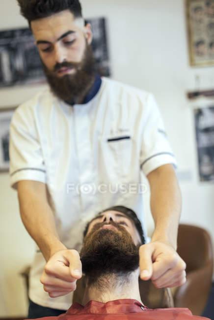 Парикмахерская, регулируя бороды мужчин клиента — стоковое фото