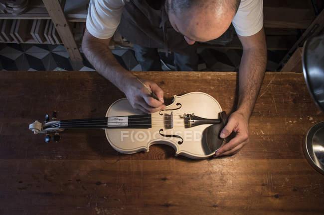 Luthier adjusting the sound post of an unvarnished violin in his workshop — Stock Photo