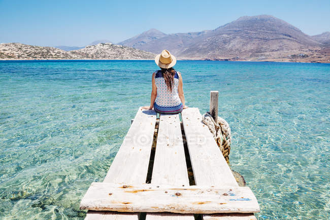 Греція, Кіклади острови, острові Amorgos, жінка, сидячи на краю дерев'яний причал, Nikouria острів — стокове фото