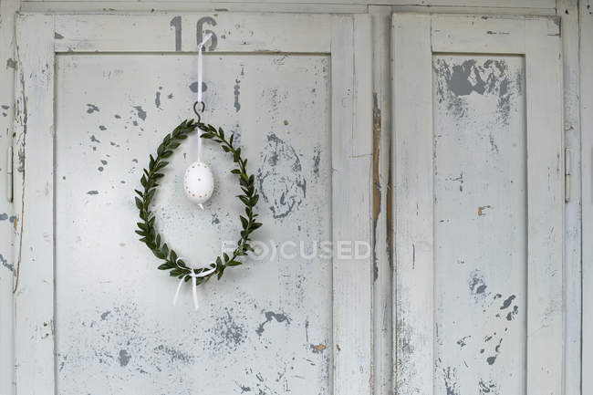 Easter egg and box tree wreath hanging in front of wooden door — Stock Photo