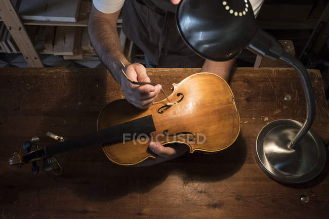 Luthier adjusting the sound post of a violin in his workshop — Stock Photo