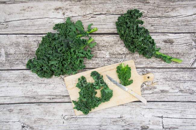 Fresh organic kale on wooden chopping board and grey wood — Stock Photo