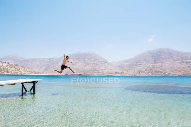 Greece, Cyclades islands, Amorgos, Aegean Sea, naked man jumping from a wooden jetty — Stock Photo