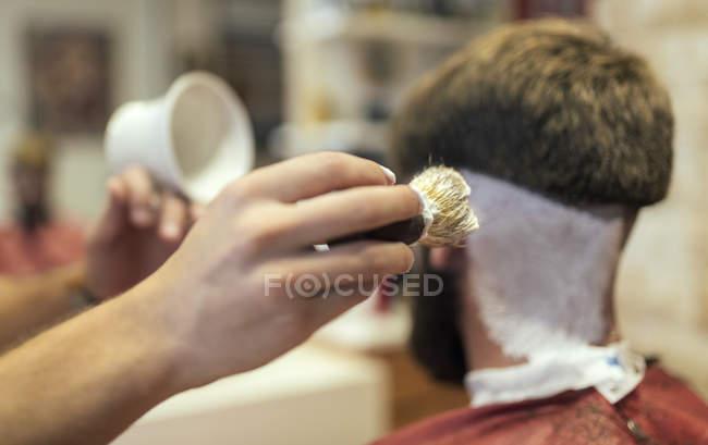 Primo piano di barbiere mani rasatura cliente — Foto stock