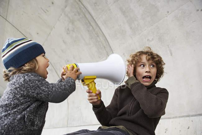 Dos hermanos jugando con un megáfono juntos - foto de stock
