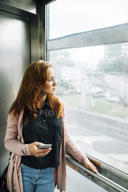 Grave giovane donna guardando attraverso la finestra — Foto stock