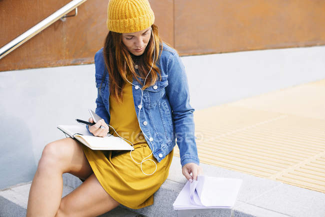 Young woman with notebook sitting on steps — Stock Photo