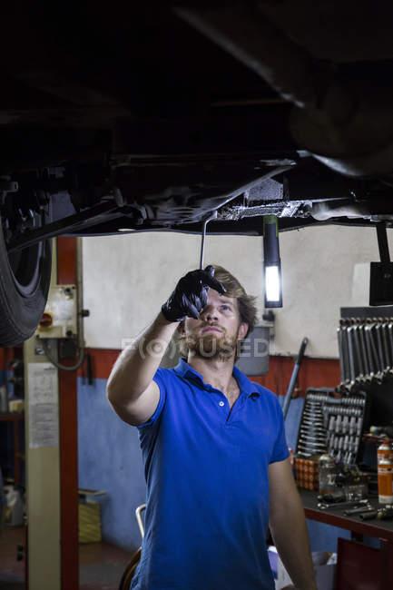 Mechaniker, die Festsetzung von angehaltenen Auto in Werkstatt — Stockfoto