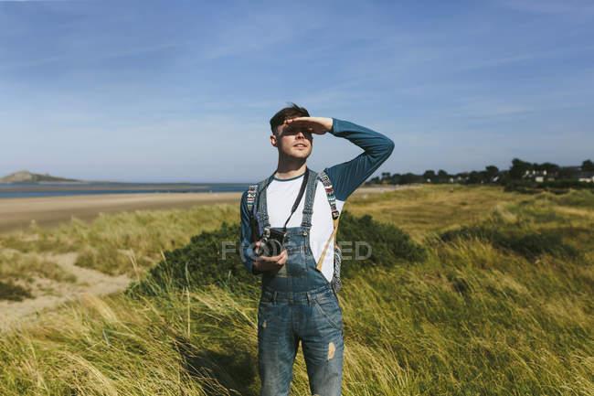 Hombre con pie de cámara en una duna - foto de stock