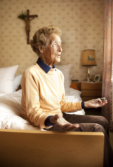 Portrait of aged woman sitting on bed in her beroom — Stock Photo