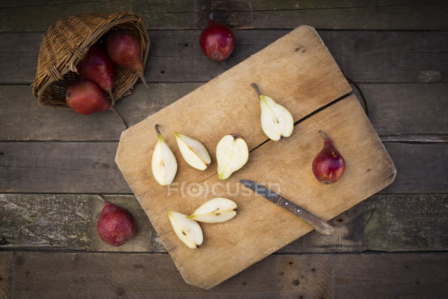 Whole and sliced organic red Clapp Favourites, wooden board and kitchen knife on dark wood — Stock Photo