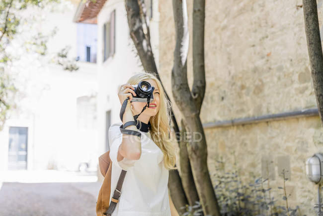 Blond woman photographing with camera — Stock Photo