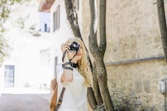 Mulher loira fotografando com câmera — Fotografia de Stock