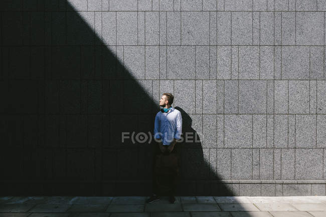 Businessman standing in front of a grey wall — Stock Photo