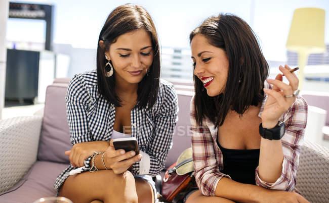 Усміхнене жіночий друзів, дивлячись на смартфон на терасі — стокове фото