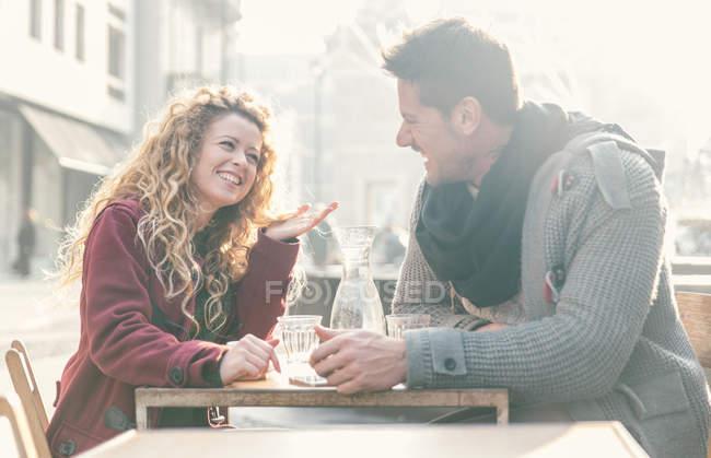Laughing couple sitting at sidewalk cafe having fun — Stock Photo