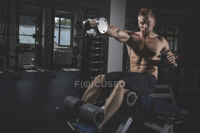 Physical athlete exercising with dumbbells in gym — Stock Photo
