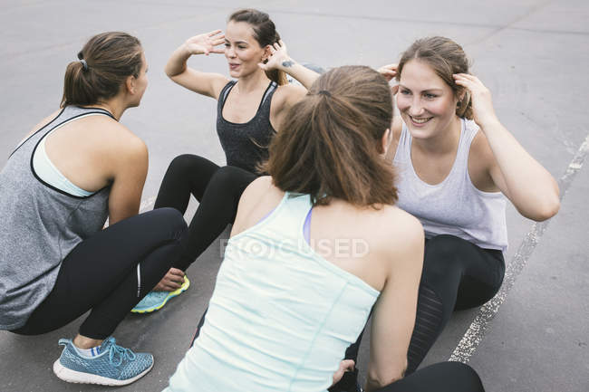 Cuatro mujeres haciendo abdominales durante la actividad de campo al aire libre - foto de stock