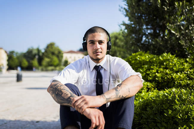 Young businessman listening music with headphones — Stock Photo