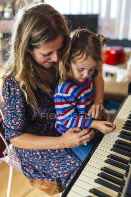 Femme et petite fille jouant ensemble du piano — Photo de stock