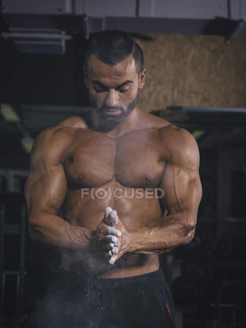 Культурист, припадає пилом руки в тренажерному залі, перед тренування — Stock Photo