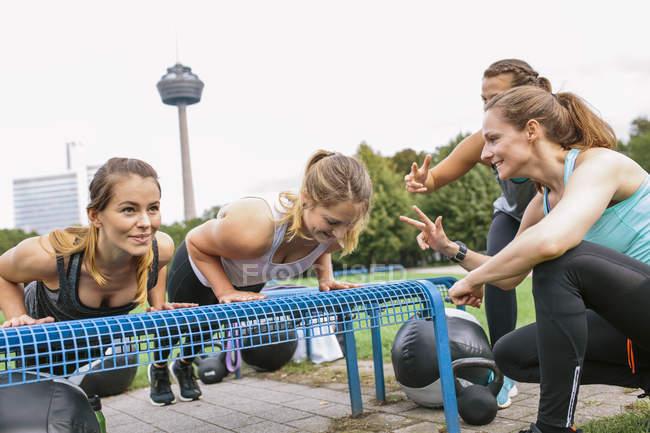 Cuatro mujeres haciendo flexiones durante campo de entrenamiento al aire libre - foto de stock