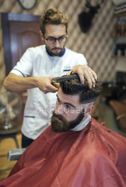 Парикмахерская стрижка волос клиента в парикмахерской — стоковое фото