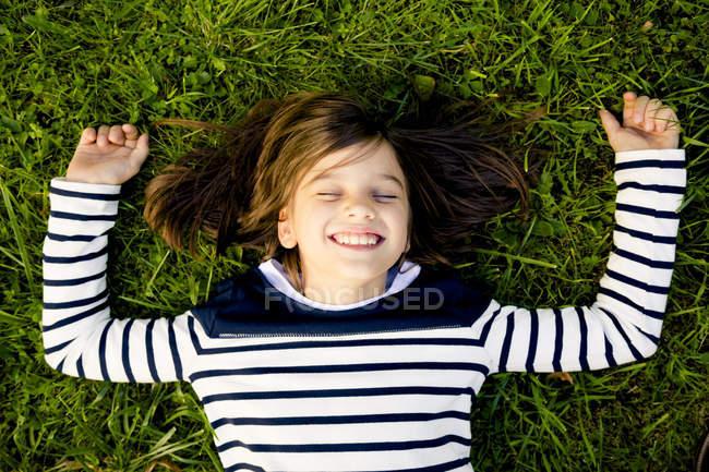 Портрет девушки в полосатой толстовке лежащей на лугу с закрытыми глазами — стоковое фото