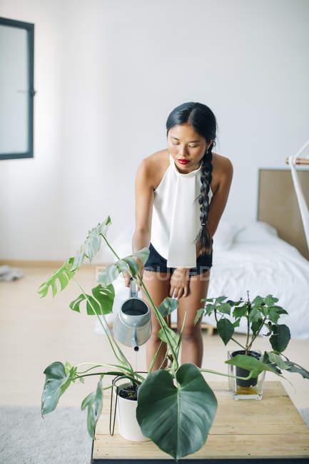 Junge Frau zu Hause Bewässerung Pflanzen — Stockfoto