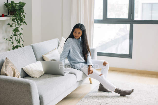Young woman sitting on couch at home looking at laptop — Stock Photo